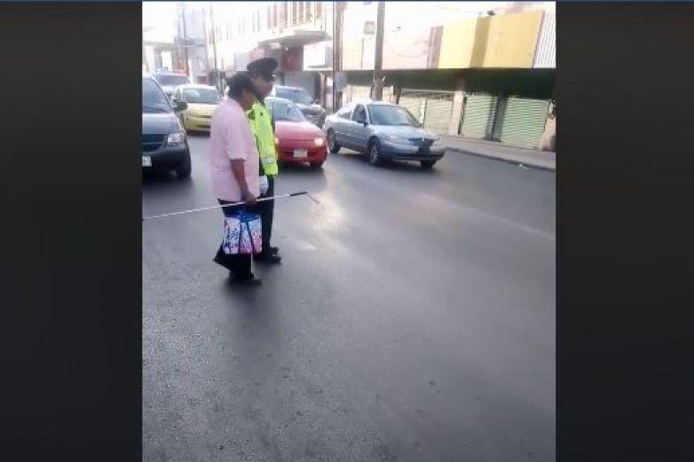 Ayuda tránsito a invidente a cruzar la calle