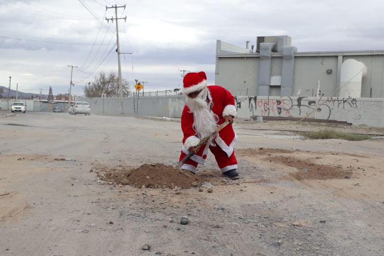 Mini Santa Claus tapa baches de la ciudad