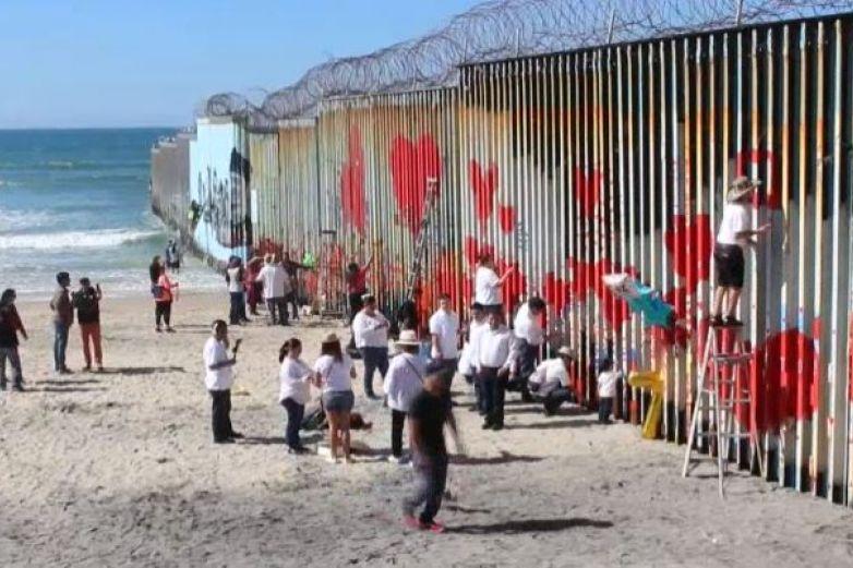 Pintan de corazones tramo del muro fronterizo