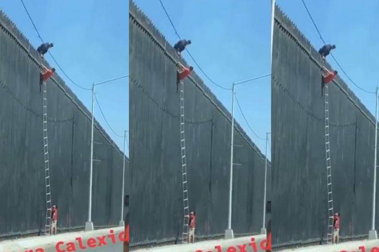Video: Captan a migrante escalando el muro con escalera colgante